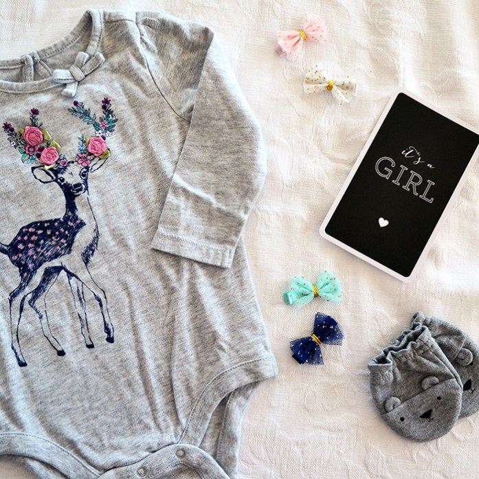 Gray deer onesie and bows to announce baby girl