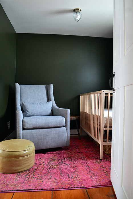 Nursery with Ikea crib, West Elm graham glider, and pink rugs with dark painted walls