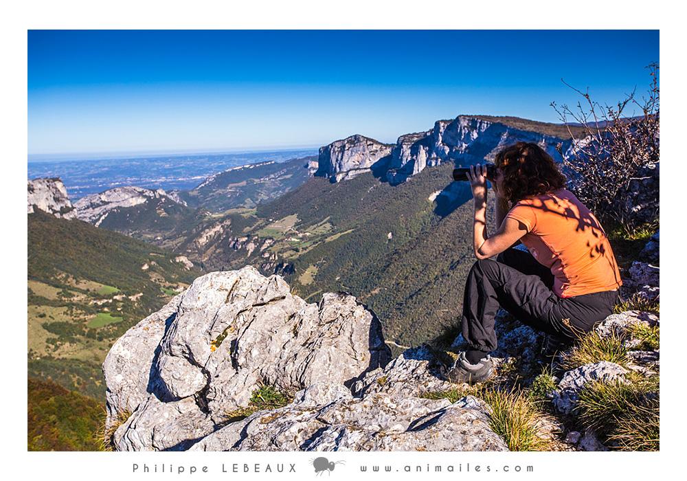 Randonneuse observant aux jumelles les animaux de montagne