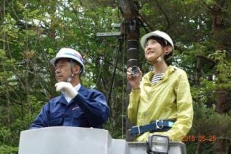 NTT東日本の保坂さんが操作する高所作業車でリポートされる森本さやかさん