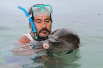 Earth Island Institute regional director Lawrence Makili with injured dolphin. (EII photo)