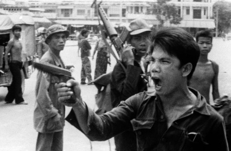 A Khmer Rouge soldier waves his pistol and orders store owners to abandon their shops in Phnom Penh, Cambodia, on April 17, 1975 as the capital fell to the communist forces. A large portion of the city's population was reportedly forced to evacuate. Photo from West German television film. (AP Photo/Christoph Froehder)
