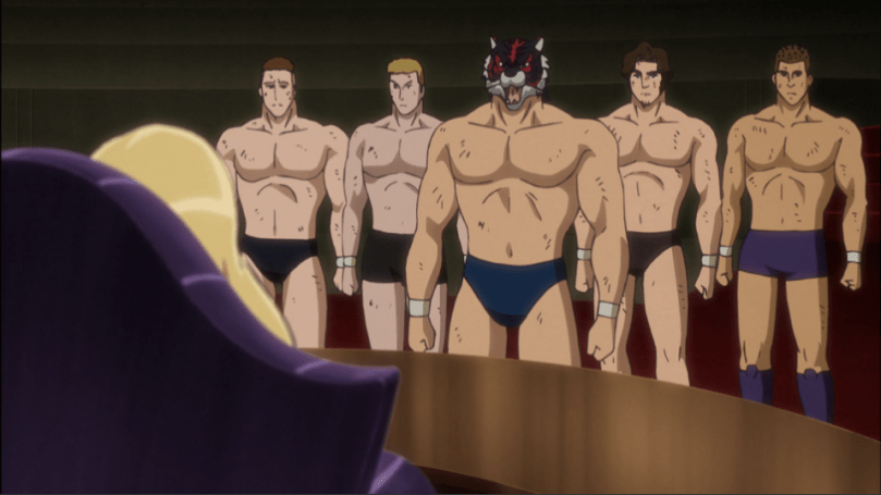 A group of men in speedos. The one in front is wearing an animal mask.