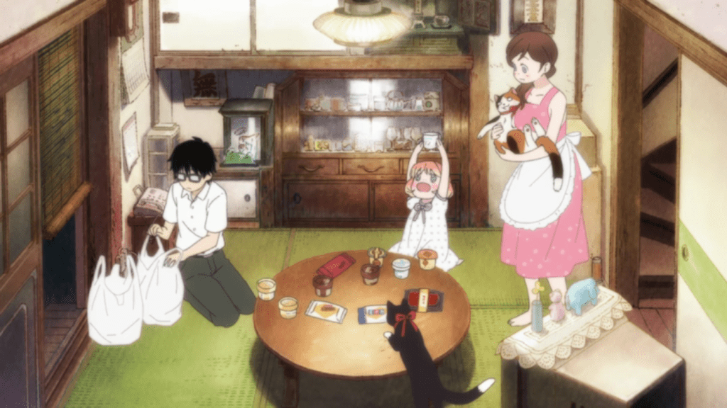 A small, cluttered Japanese-style dining room. A teen boy sits on the ground next to grocery bags while a young woman enters the room, carrying a cat. A small girl sits at the round table, holding aloft a teacup.