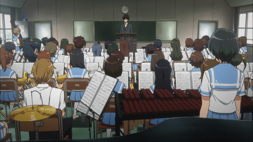 We are at the back of a classroom with the members of a school orchestra in front of us, looking up at their teacher, a man with dark hair and in a dark suit standing on a conductor's podium in front of a blackboard.
