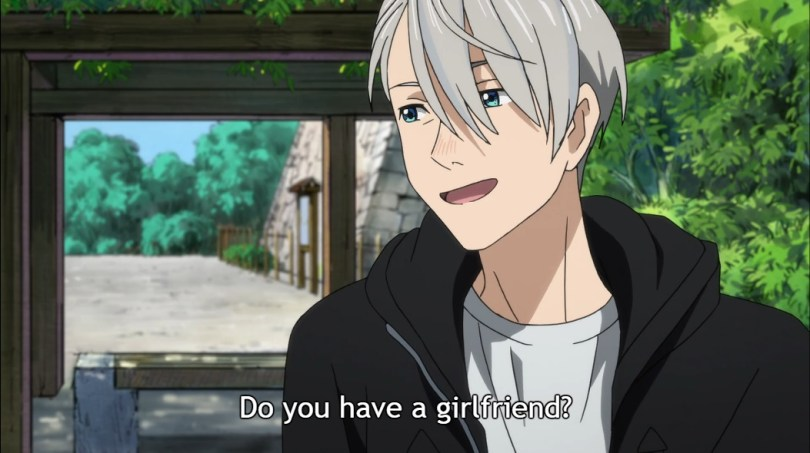 """Victor sits on a bench outside in Hasetsu, smiling as he talks to Yuri, who is off screen. Subtitle: """"Do you have a girlfriend?"""""""