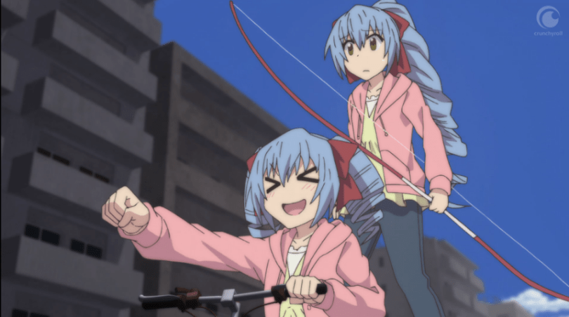 Twin girls with matching blue hair, jeans and pink jackets, move forward on a bicycle ridden by the twin in front, who looks excited, while the twin behind her holds a large bow and looks concerned.