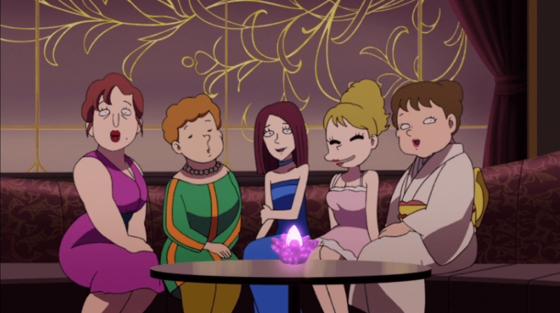 Five women with various body types, hairstyles and styles of dress sit around a table and smile.