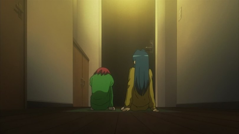 Two girls shown from behind sitting in a hallway in front of a door; the blue-haired one is leaning back and while the red-haired one is curled forward, knees pulled to her chest.