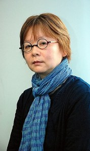 A photo of Nakayama Kaho, an older woman with round glasses and reddish hair, wearing a scarf