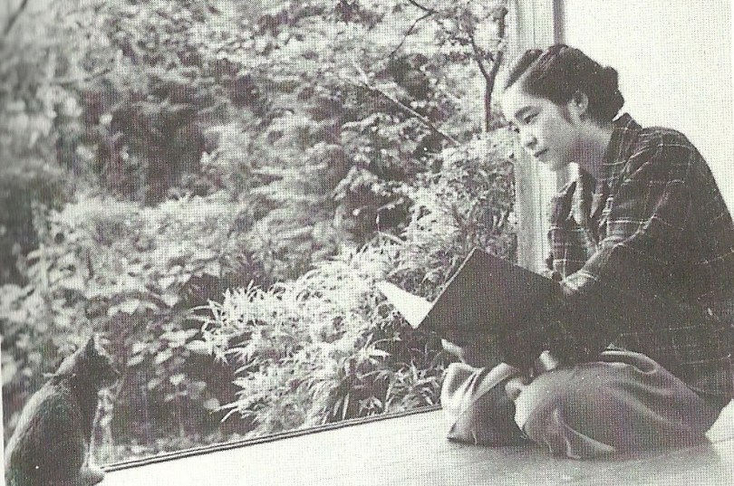 A black-and-white photo of a young Japanese woman sitting on a Japanese-style porch, a sketchbook in hand, looking at a cat sitting on the other side of the porch. There are trees and plants in the background.