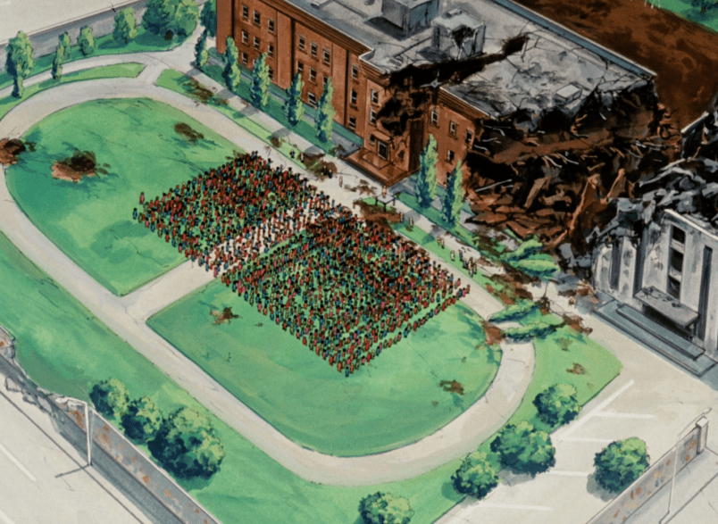 An overhead shot of a school building that's taken heavy damage, one side caved in. On the school grounds in front of the building are straight rows of people, too small to see details from this height.