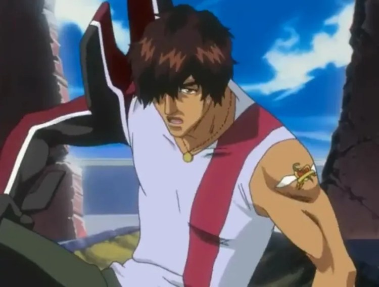 A mid-shot of a well-muscled, brown-skinned man (Chad) with fluffy hair falling over one eye and a tattoo on one shoulder couching as if ready to fight