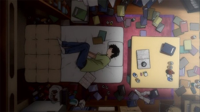 A young man is curled up on his side on a bed with his hands between his legs. His room, seen from above, is a mess, littered with trash, notebooks, empty cans, and other items.
