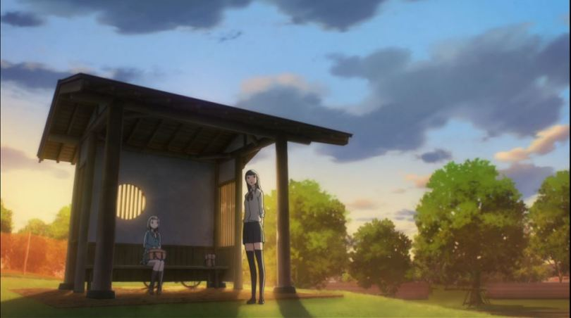 wide shot of Mari and Shirase standing under a bus stop at sunset