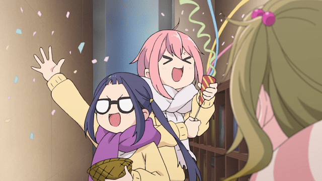 Two teen girls in scarves and coats looking excited: One is throwing confetti while the other is pulling a party poppy, streamers flying from it.