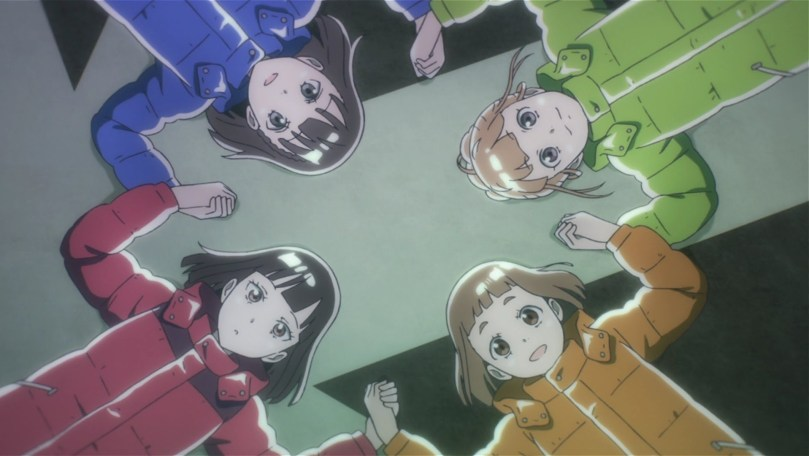 Four teen girls wearing mulitcolored winter coats lay on their backs, holding hands and looking upwards.