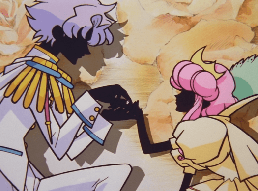 A young girl in a princess dress receives a ring from a young man in prince clothes. They are shadow-puppets, without facial features.