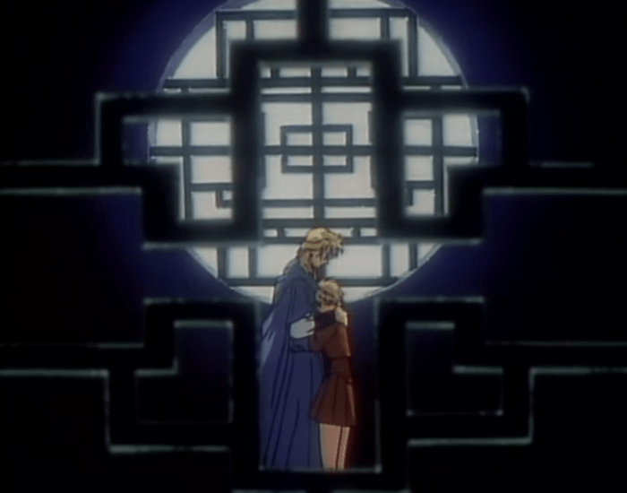 Yui and Nakago embrace each other in a darkened room full of latticework windows and doorways, giving the scene a darkened, claustrophobic air.