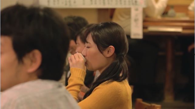 live action Wakako taking a drink in a crowded dining hall.