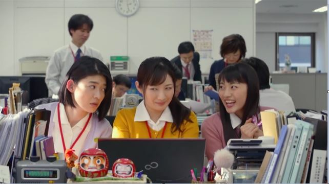 live action Wakako at her job, two of her coworkers leaning in on either side of her