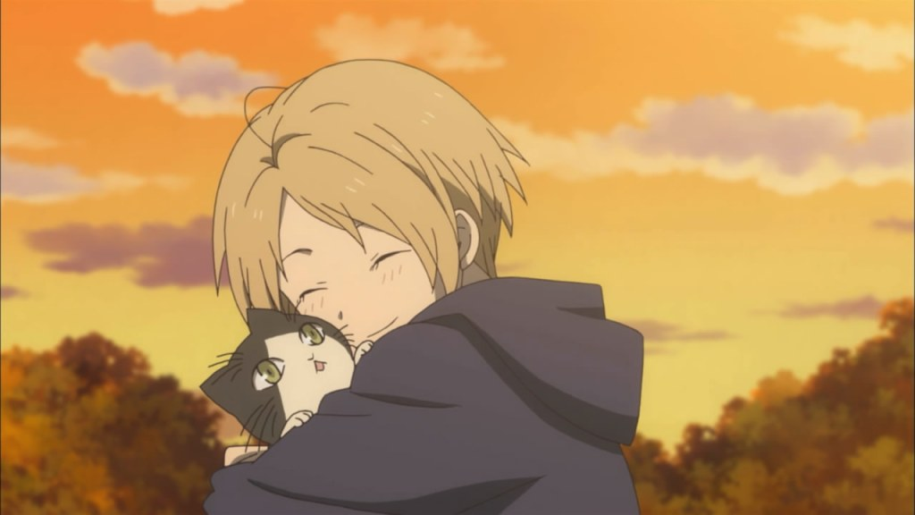 A young Natsume hugs a kitten at sunset.