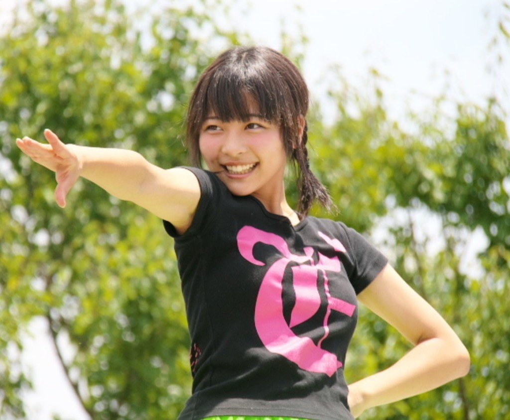 Photo of a young Japanese woman in a T-shirt smiling and striking a pose.