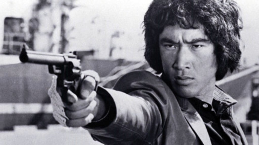 A black-and-white photo of Yusaku Matsuda pointing a gun