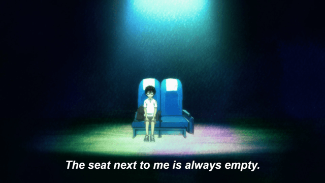 "A boy sits in a theatre chair next to one other, empty theatre chair. He is under a spotlight and surrounded by darkness. Subtitles read: ""The seat next to me is always empty."""