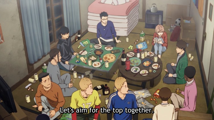 "A group of young men sit around two low tables full of food and drinks. Subtitles read ""Let's aim for the top together!"""