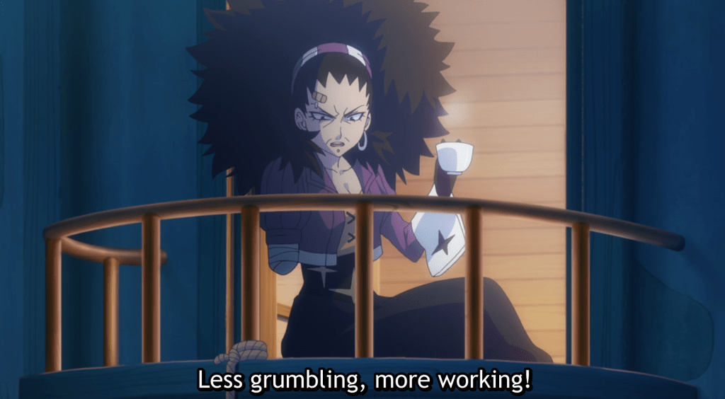 "An older woman with fluffy hair holds a cup of tea in one hand. She is missing her other arm. She sits on a balcony and says ""Less grumbling, more working!"""