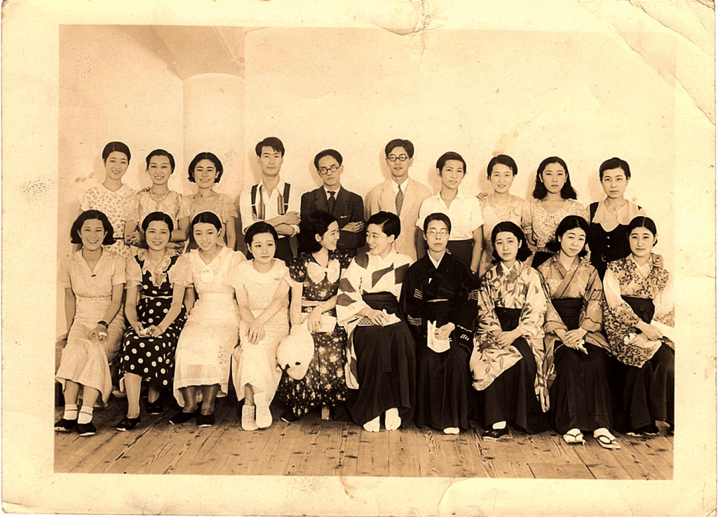A group photo of a little over a dozen young women flanking three young men.