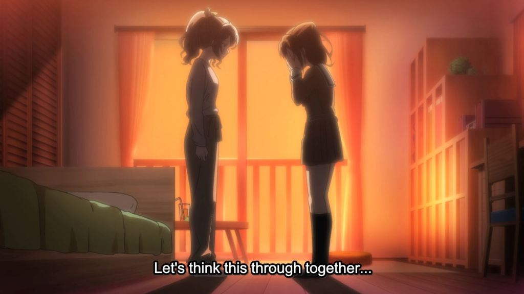 "Two girls stand in a bedroom dimly lit by the setting sun. Saya stands with her hands limply to her side as Kasumi holder her hands up to her face. Subtitles: ""Let's think this through together..."""