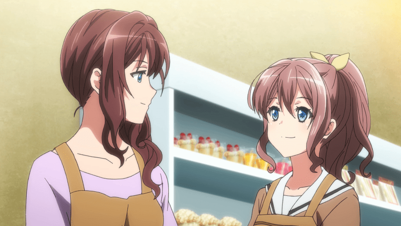 Saya and her mom stand in a bakery, looking at each other and smiling