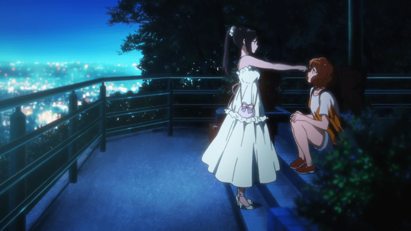 Reina in a white dress reaching out to touch Kumiko's forehead on top of a hill