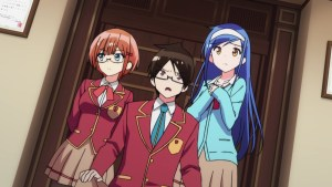 Two girls stand beside a boy who looks shocked. They wear school uniforms.