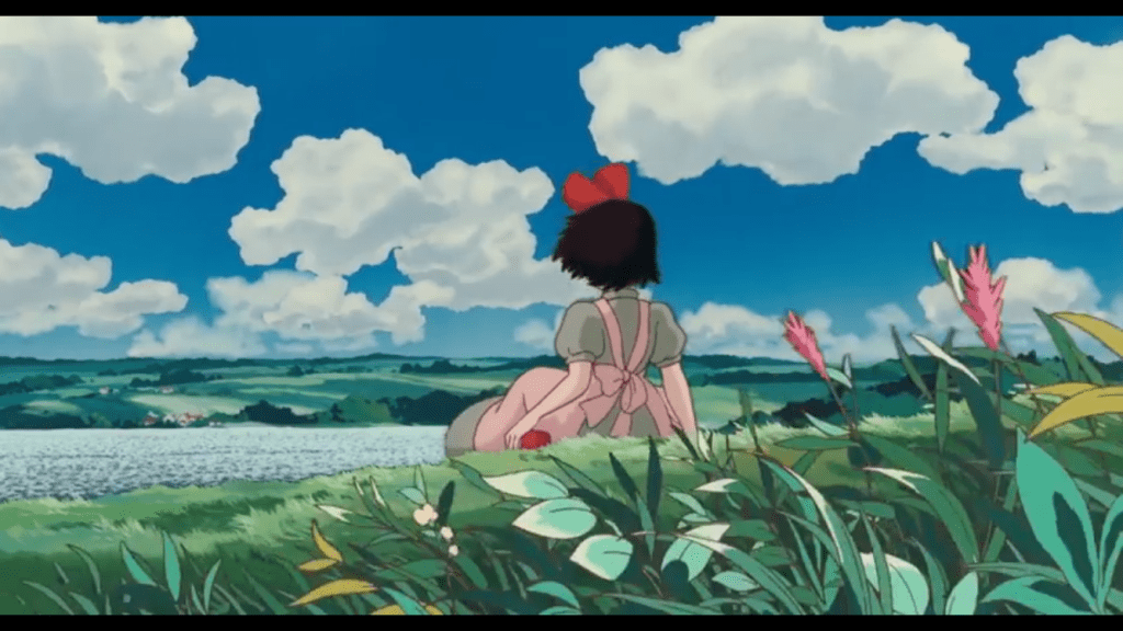 Kiki sitting on a hill looking across a lake