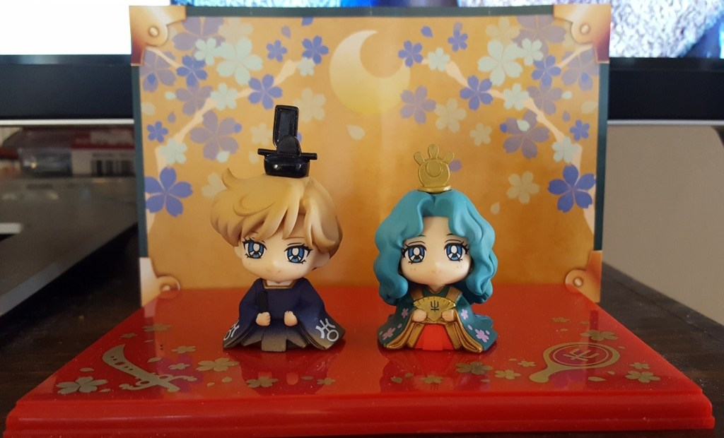 A photo of two figurines wearing Japanese imperial garb, Haruka wears formal men's robes and Michiru wears a multilayered women's robe.