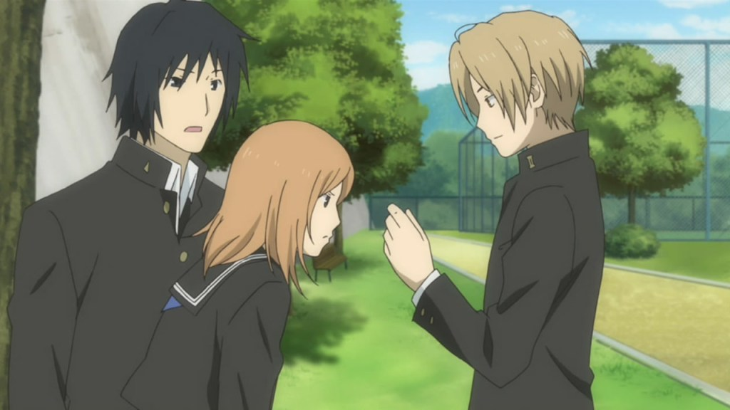 Natsume holds something in his hands that his two friends study