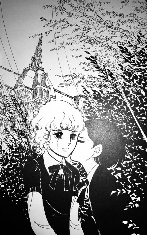 Juli kissing a crying Oskar's cheek against a background of trees and the school