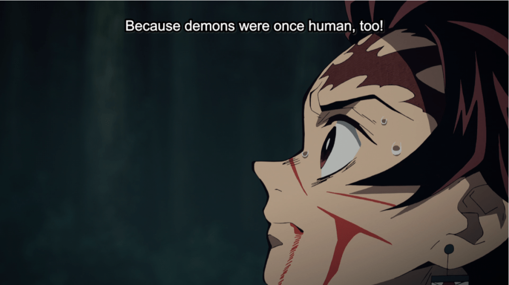 Close-up of a bleeding Tanjiro. Subtitle: Because demons were once human, too!