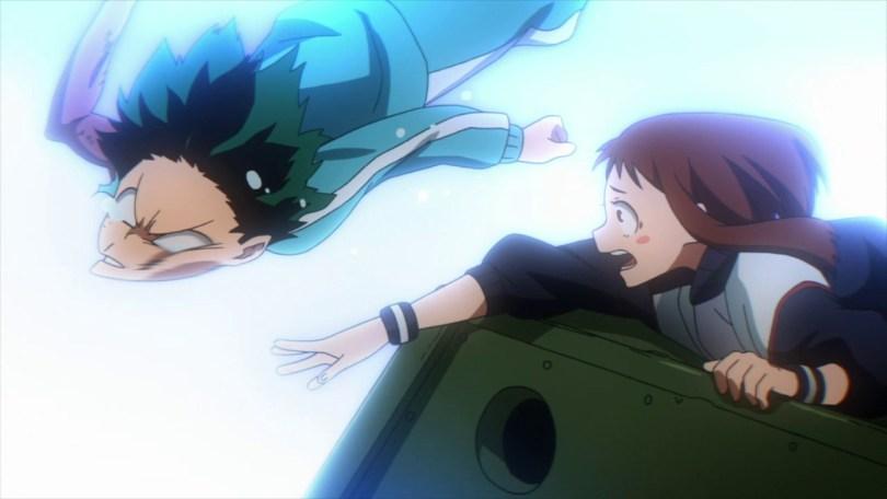 Uraraka reaches forward over the top of a tank and smacks Deku's face as he's falling