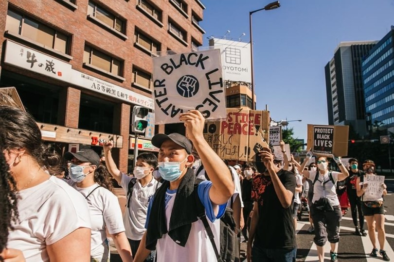 A scene from the Osaka protest. People walk in the street holding signs stating the importance of Black lives.