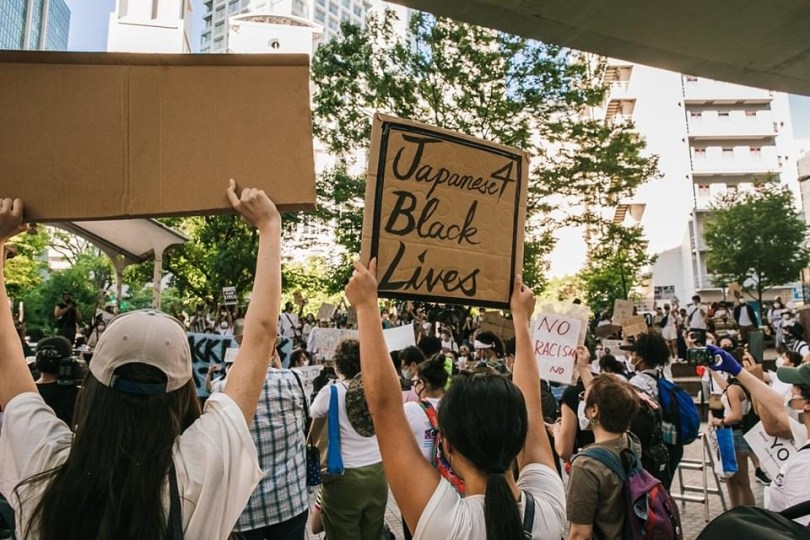 """A shot from behind of protestors. The photo focuses on a sign reading """"Japanese 4 Black Lives"""""""