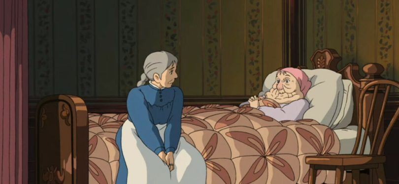 Sophie sitting on the edge of the Witch's sickbed, the Witch appearing as a small old woman