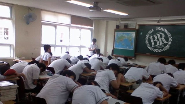 Students at Miyashima Senior High School take the oppurtunity to nap during the announcement that their class will partake in this year's Battle Royale.