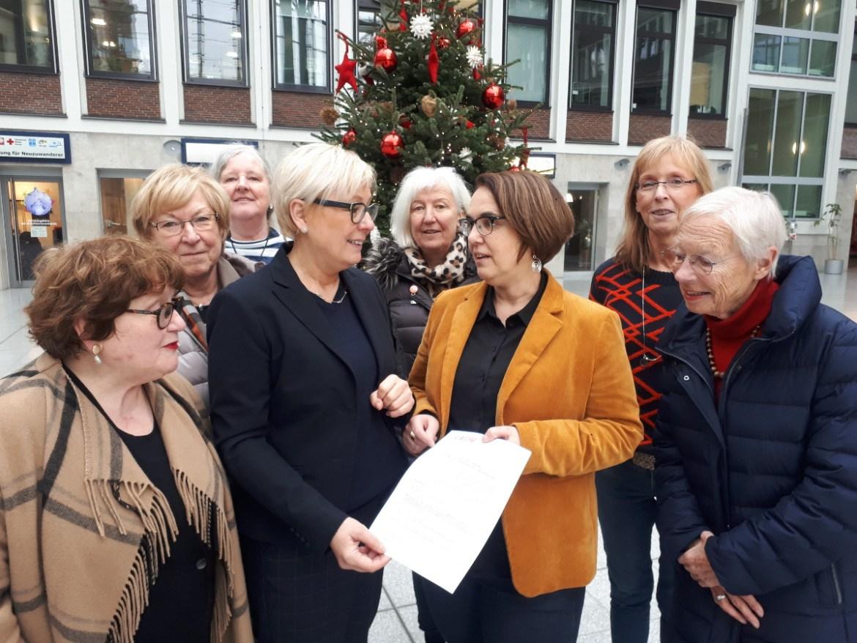 Justine Grollmann, Vorsitzende der AG Dortmunder Frauenverbände (4.v.l.) überreicht Anja Butschkau (3.v.r.) einen Beschluss, der die Einführung eines Paritätsgesetzes fordert.