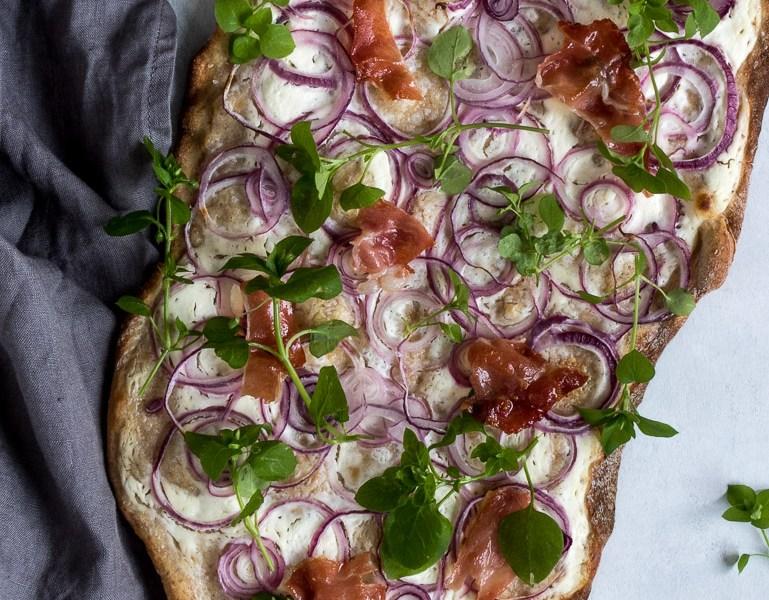 Flammkuchen med rødløg, serano og ukrudtssalat