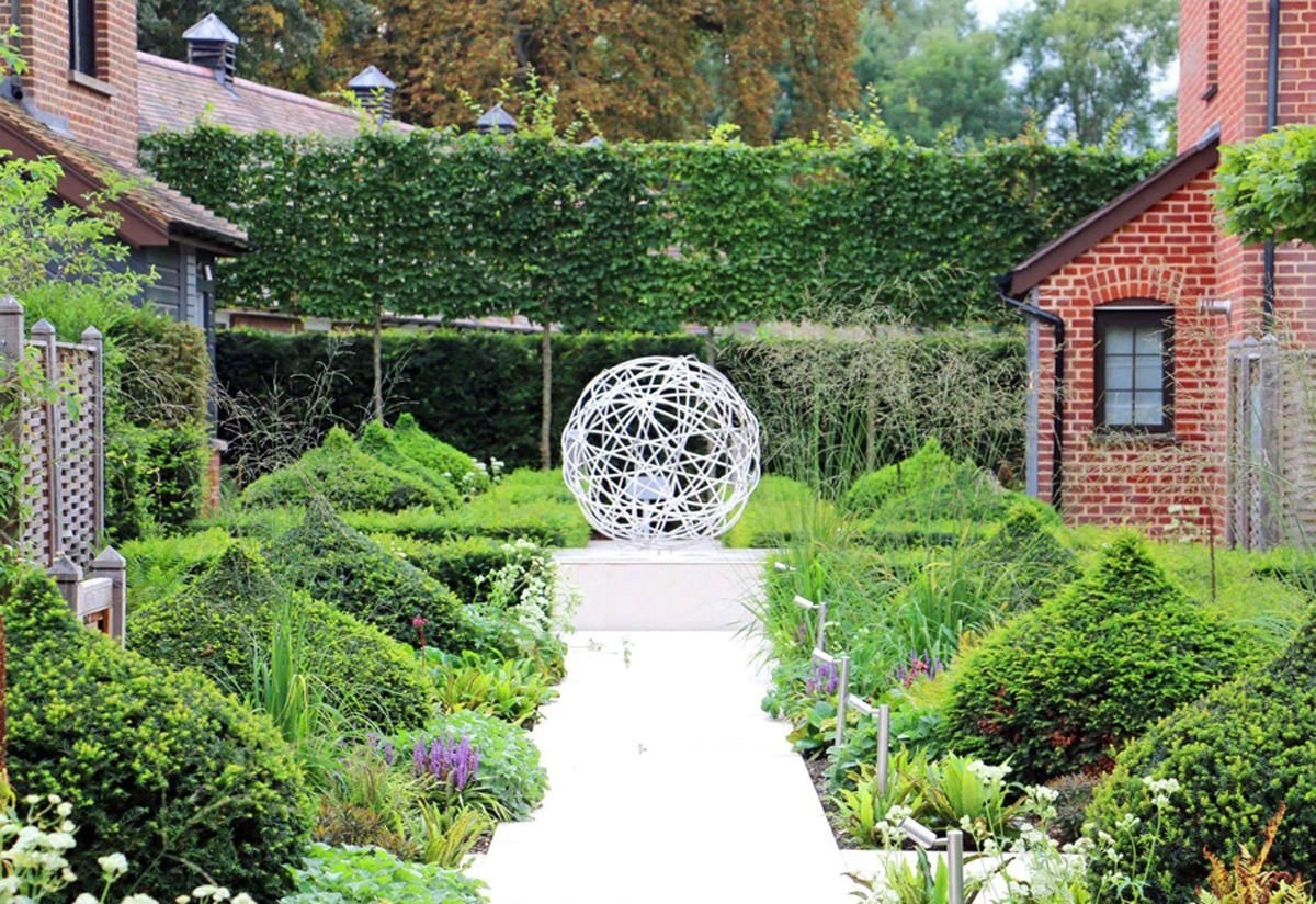 Clipped yew onion-shaped topiary cushions lining porcelain path leading to feature sculpture and pleached hornbeam trees