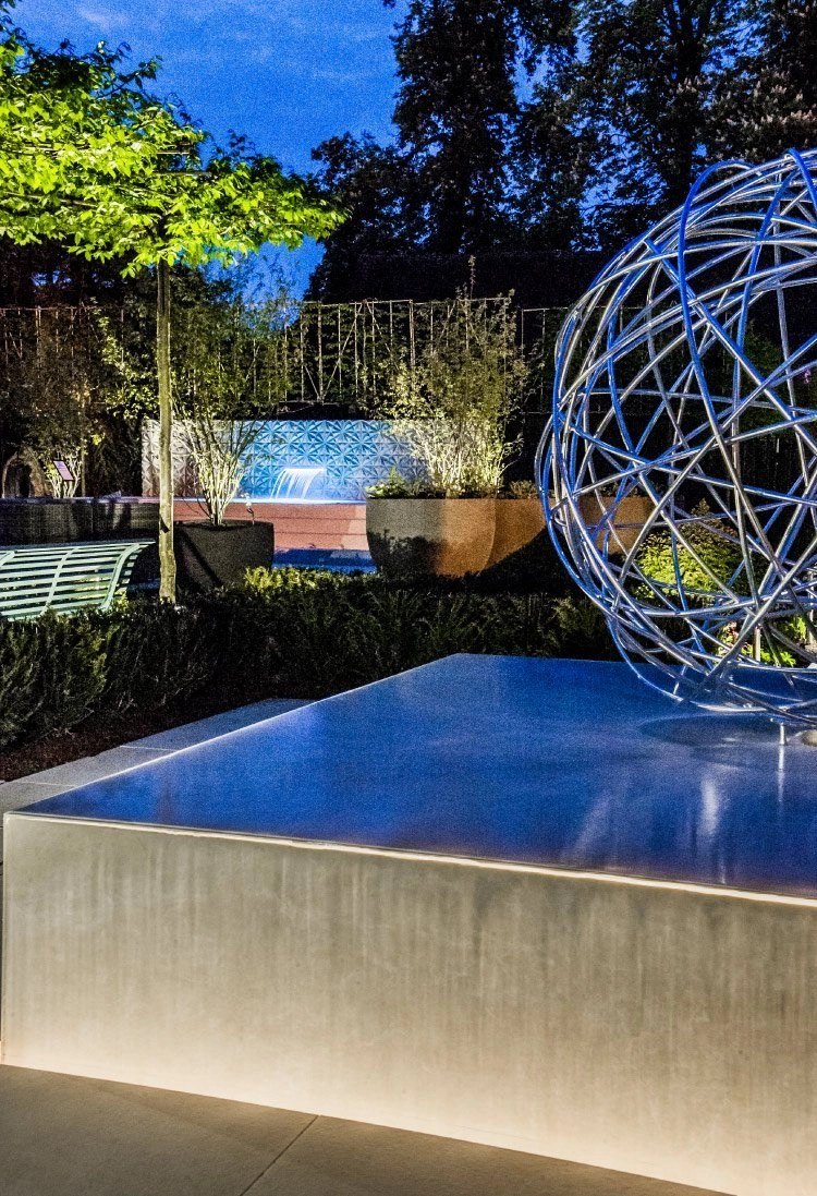 Luxury spa garden at night with dramatic water features designed by Ann-Marie Powell Gardens